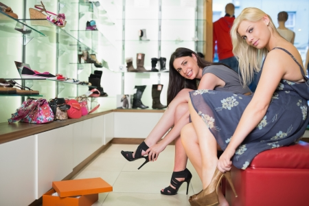 Women trying shoes on  smiling in shoe shop