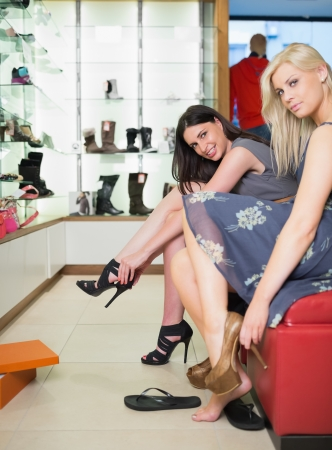 shoe store: Women smiling and trying on shoes in shoe store