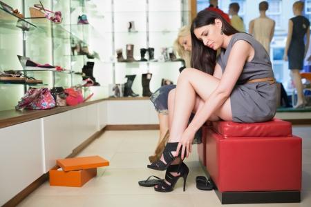 comprando zapatos: Mujer tratando de zapatos de color negro sentado en una tienda