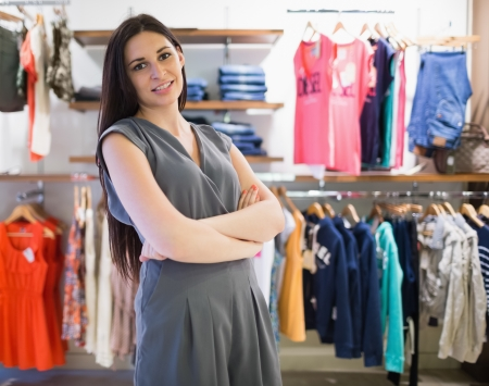 Woman in clothes store with arms folded photo