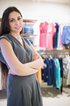 Woman in clothes shop with arms crossed photo