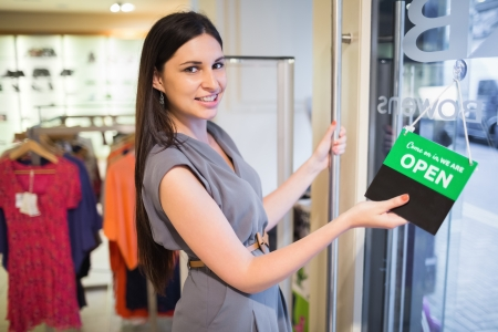 Woman opening clothes store at door with sign photo