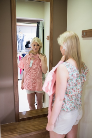 Woman is looking in mirror holding up shirt Stock Photo - 15593458
