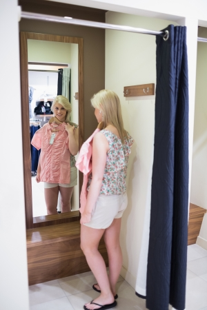 Woman looking in the mirror standing in the changing room  photo
