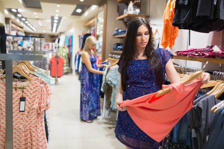 Woman standing in a shop looking at clothes Stock Photo - 15593478