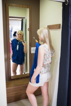 checkout stand: Woman standing in front of a mirror in the changing room