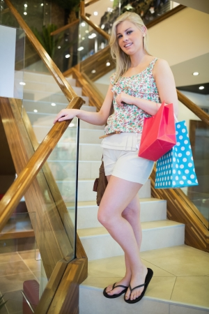 checkout stand: Woman is standing at the stairs in a shopping mall