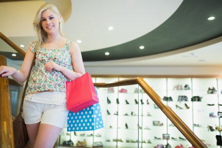 Woman standing at a shopping mall on the stairs holding bags photo