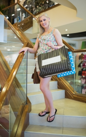 Woman standing in shopping mall at the stairs of a shop smiling  photo