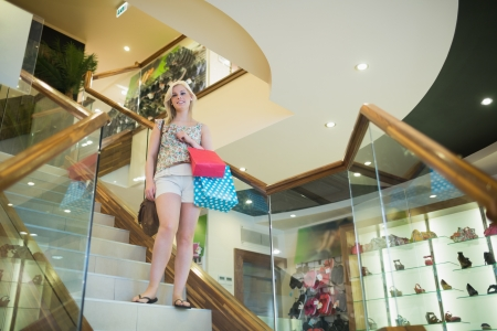 Woman standing on the stairs of clothes store looking down  photo