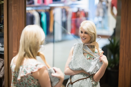 Woman is looking in the mirror at the boutique Stock Photo - 15585054