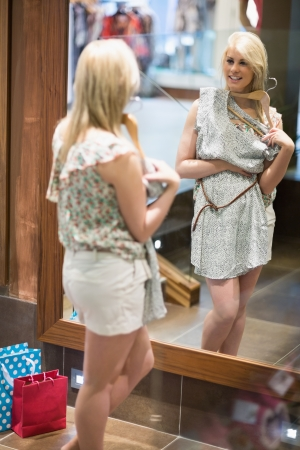 Woman smiling in a boutique while standing in front of a mirror Stock Photo - 15584319