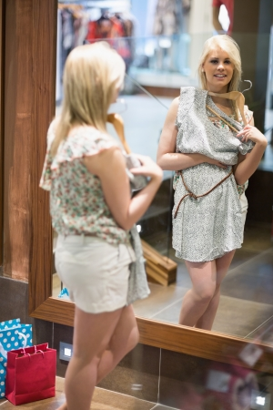 Woman is looking in the mirror at the changing room smiling Stock Photo - 15584299