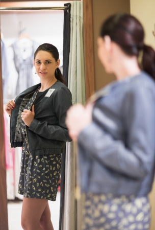 Woman trying on jacket and smiling in changing room photo