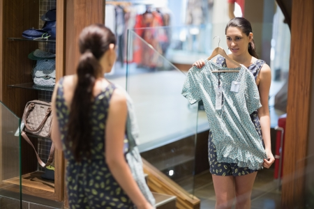 Woman is looking at the mirror while holding up clothes in the changing room  Stock Photo - 15584979