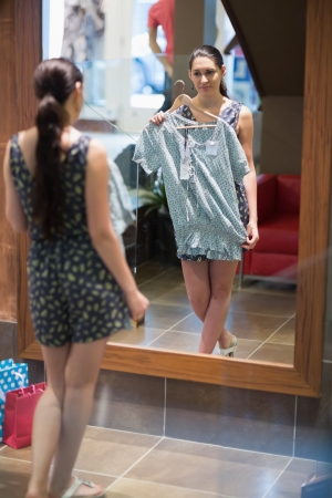 Woman is standing in front of the mirror with clothes in the changing room Stock Photo - 15585050