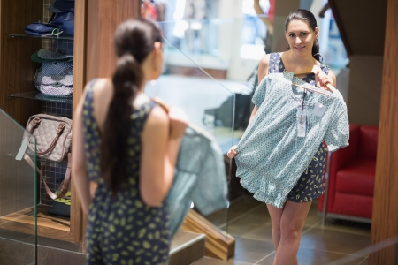Woman smiling in the mirror in clothes store Stock Photo - 15584364