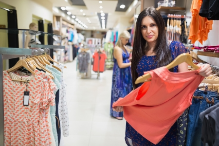 Woman in clothes shop looking at clothes and smiling Stock Photo - 15593431