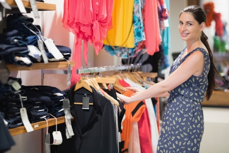 Woman standing at a clothes rail in the clothes store Stock Photo - 15593350