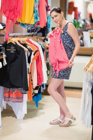 Woman is standing at the clothes rack at the shop holding up shirt Stock Photo - 15593053