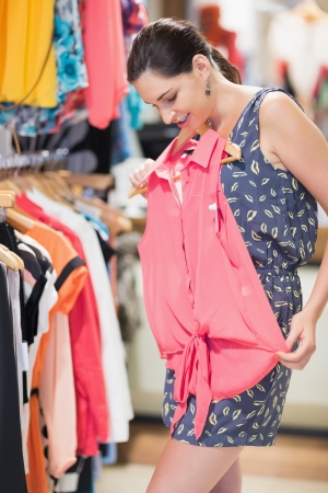 product range: Woman looking at shirt in clothes store Stock Photo