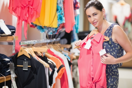 Woman in clothes store looking at pink shirt  and smiling Stock Photo - 15593306