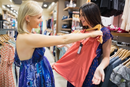 burrowing: Woman holding shirt up to friend in clothes store