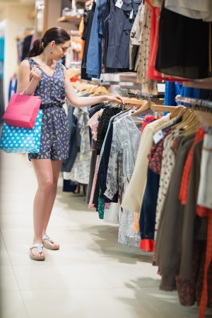Woman is standing at the clothes rack  holding bags in the boutique Stock Photo - 15593173
