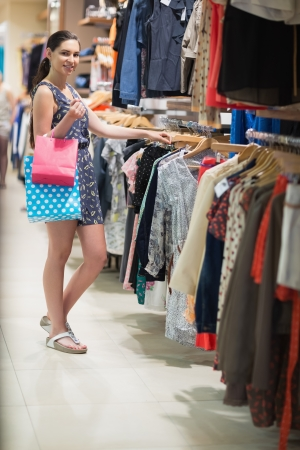 Woman is standing at the clothes rack searching in the shopping mall Stock Photo - 15593117