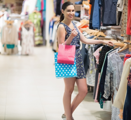 Woman standing at the clothes rack of the boutique holding two bags Stock Photo - 15591284
