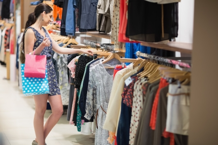 Woman searching through clothes holding two bags in clothes store Stock Photo - 15593520