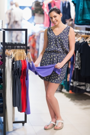 Woman smiling and looking at clothes in shopping mall Stock Photo - 15592893