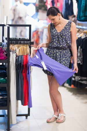 Woman looking at purple shirt in shopping mall Stock Photo - 15593000