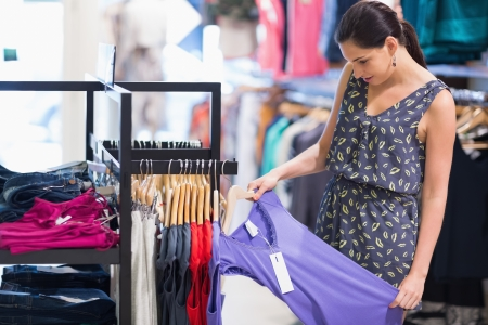 Woman is looking at price tag of purple shirt in shopping mall photo