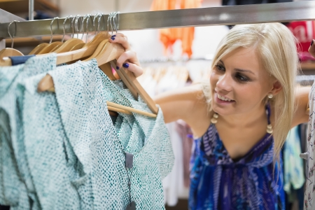 Woman  standing at the clothes rack smiling  photo
