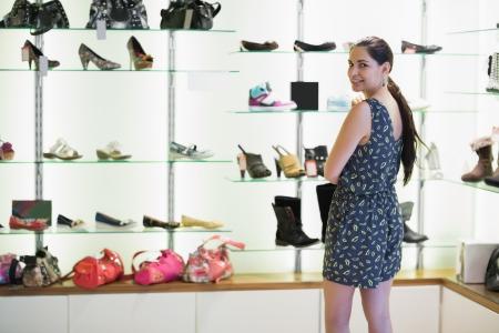 comprando zapatos: Mujer de pie al lado de la pantalla de zapatos en centro comercial Foto de archivo