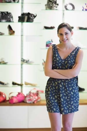 Woman  standing in front of shoe display with arms folded photo