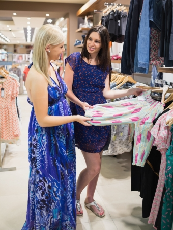 checkout stand: Women  standing at a clothes rail and smiling at a shopping mall