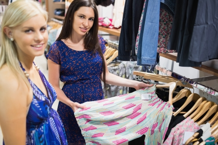 Women looking through clothes and smiling in shopping mall Stock Photo - 15584356