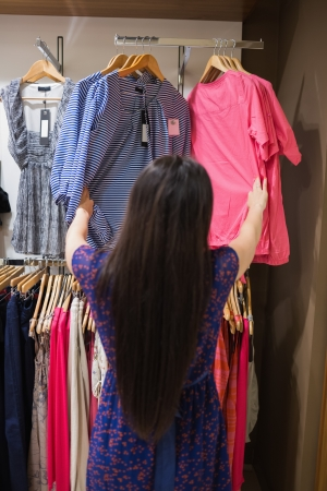 Woman looking through clothes rail in shopping mall Stock Photo - 15584942