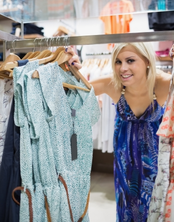 Woman smiling and looking through clothes rail in shopping mall Stock Photo - 15593328