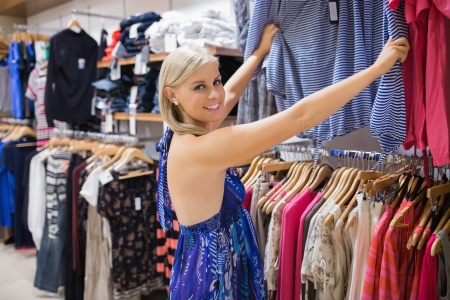 Woman  looking through clothes and smiling in shopping mall photo
