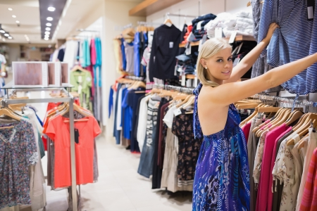 Smiling woman looking through clothes at the boutique Stock Photo - 15584980