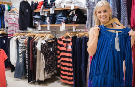 Smiling woman holding up blue shirt in boutique Stock Photo - 15593183