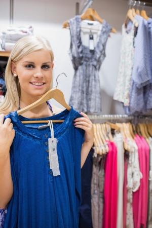 Happy woman holding up blue shirt in clothes store photo