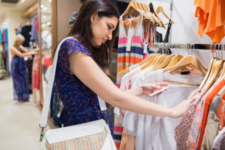burrowing: Woman with bag looking through clothes in shopping mall Stock Photo