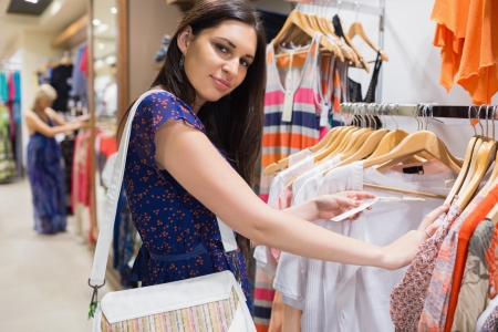clothing rack: Woman with bag looking through clothes and smiling in shopping mall