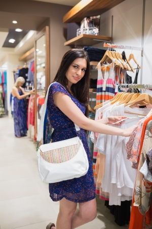 Smiling woman looking through clothes in shopping mall photo