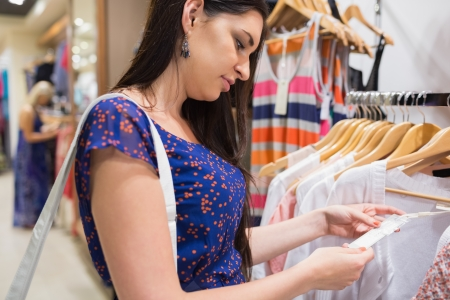 Woman looking at price tag of clothes in shopping mall photo