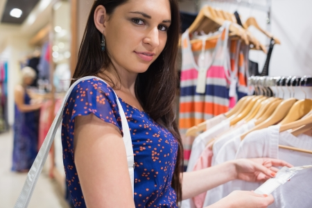 Woman holding price tag and smiling in clothing store photo